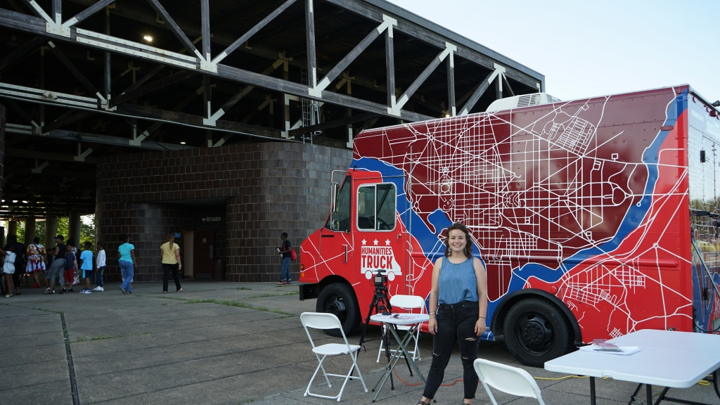 Maren Orchard stands outside the Humanities Truck with the oral history set up.