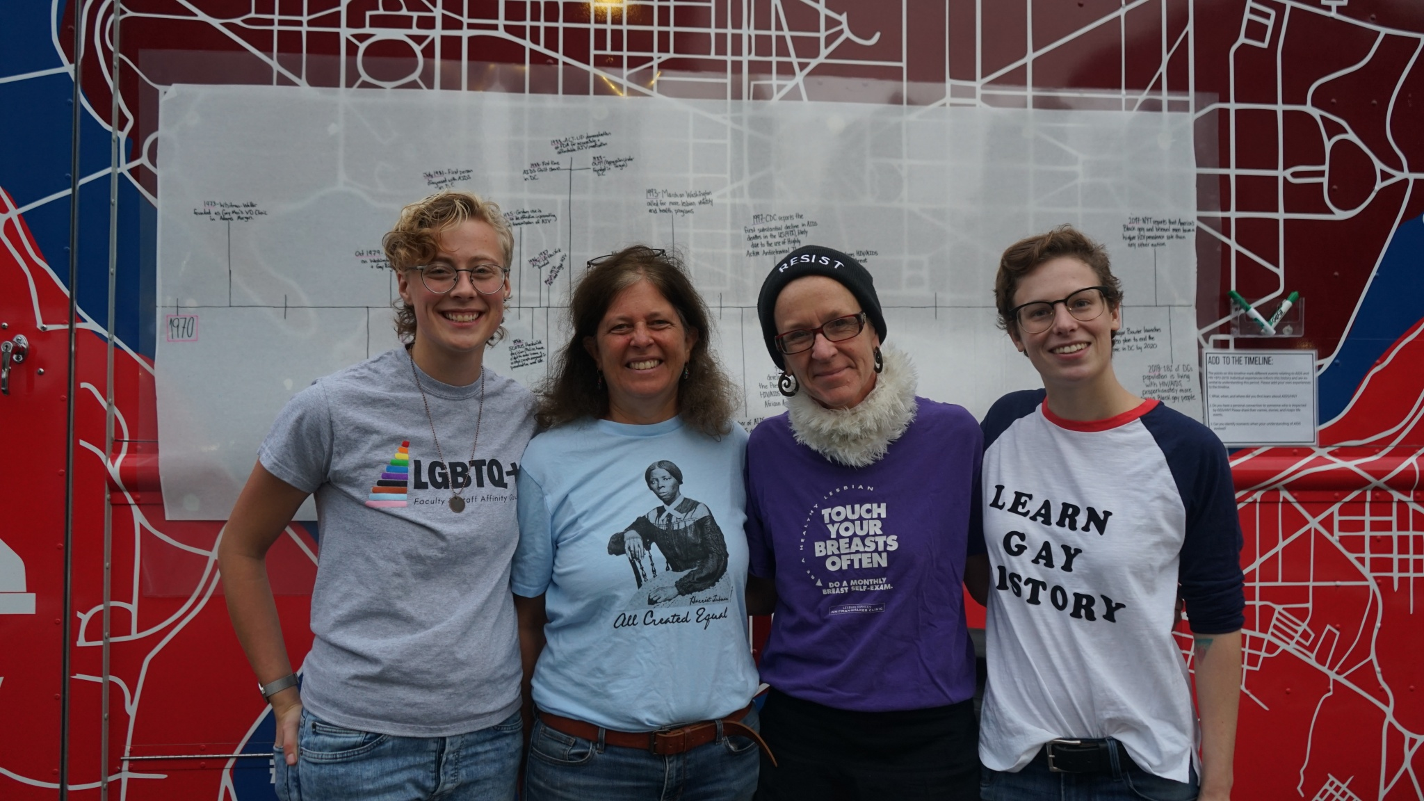 Photo of the team in front of timeline; from left to right: Kai W, Mary Ellen, Amelie, and Haley S.